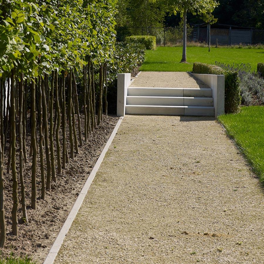 Een tuinpad aangelegd uit dolomier, met een trapje in het midden tussen het gras.